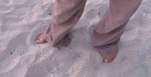 Feet in the sandy beach in Naples Florida